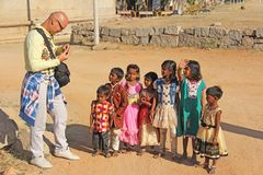 India, Hampi, 02 February 2018. A bald and cheerful European man gives gifts to Indian children. Joyful children are pulling their. Hands for gifts. Hampi stock image