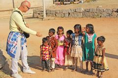 India, Hampi, 02 February 2018. A bald and cheerful European man gives gifts to Indian children. Joyful children are pulling their. Hands for gifts. Hampi stock photos