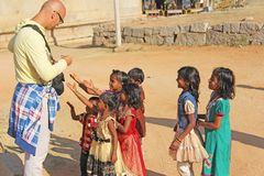 India, Hampi, 02 February 2018. A bald and cheerful European man gives gifts to Indian children. Joyful children are pulling their. Hands for gifts. Hampi stock photography