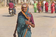 India, Hampi, February 2, 2018. An elderly woman in a sari is walking along the street of Hampi village. The Indian woman is royalty free stock photography