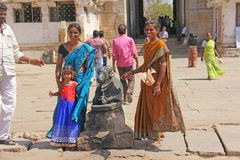 India, Hampi, 01 February 2018. Indian women and children are posing next to a figure or statue of a connected cow.  stock image