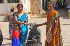 India, Hampi, 01 February 2018. Indian women and children are posing next to a figure or statue of a connected cow.  stock photo