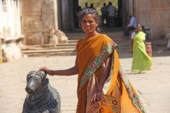 India, Hampi, 01 February 2018. Indian women posing next to a figure or statue of a connected cow.  royalty free stock images