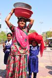 Patan: Indian woman with her two daughters carring water bowls o royalty free stock images