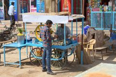 Seller of juice of sugar cane near press and buyer. India, Jaisalmer - March 5, 2018 seller of juice of sugar cane near press and buyer royalty free stock photos