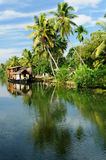 India - Kerala canal. Coco trees reflection and beautifoull house boat at back waters of Kerala, India Stock Photography