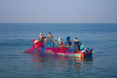 India, Kerala - December 27, 2015: Indian fishermen graphically pull painted Seine right in boat 2. Net painted in bright colors, Stock Photos