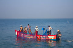India, Kerala - December 27, 2015: Indian fishermen graphically pull painted Seine right in boat 2. Net painted in bright colors, Royalty Free Stock Photos