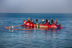 Indian fishermen graphically pull painted Seine right in boat 2. royalty free stock photography
