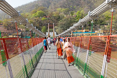 INDIA, LAXMAN JHULA - APRIL 8, 2017: People walking on the suspe Royalty Free Stock Image