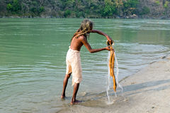 INDIA, LAXMAN JHULA - APRIL 17, 2017: Sadhu washing clothes at t Stock Images