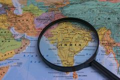Map of India through magnifying glass on a world map. India map through magnifying glass on a world map Royalty Free Stock Photos