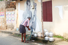 The india men pump water to tank for home. It is the culture of Kochi, South India, u can see often on the side of local street stock images