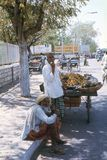 1977. India. An old man sitting on a footpath, smoking his chillum-pipe. Stock Photo