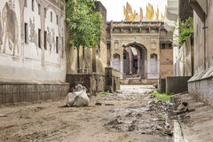 India, old semi-abandoned road in Rajastan. Old semi-abandoned road in Rajasthan with a cow resting in the mud Royalty Free Stock Image