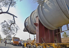 India roadways traffic congestion jam accide. A heavy goods transporter has his cargo stuck between two trees on either side of a tree lined road and road crew stock image