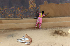 India's Tribal Lifestyle. A tribal woman plastering mud wall in a remote village of West Bengal stock photography