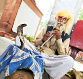 India Snake charmer. Indian hindu Snake charmer adult man in turban playing on musical instrument before snake at a basket Royalty Free Stock Image