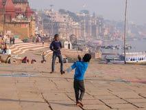 india varanasi Ungar som spelar badminton på flodstranden i Varanasi, Indien arkivfoto