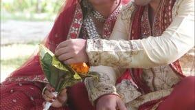 India Wedding Ceremonia. Bride and groom stroking bouquet