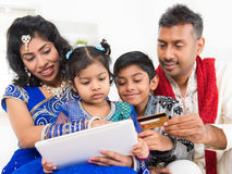 Indian Asian family online shopping with credit ca. Indian Asian family using digital tablet pc computer online shopping with credit card at home. India family Stock Photo