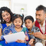 Indian Asian family online shopping. Indian Asian family using digital tablet pc computer online shopping with credit card at home. India family living lifestyle Stock Images