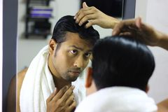 Indian asian man looking after his appearance in front of a mirror beauty styling lifestyle.hair styling. S Stock Image