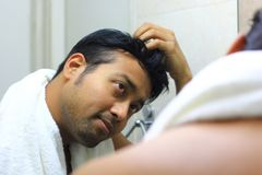 Indian asian man looking after his appearance in front of a mirror beauty styling lifestyle.hair styling. S Royalty Free Stock Photography