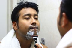 Indian asian man looking after his appearance in front of a mirror beauty styling lifestyle. Shaving routine. S Stock Photography