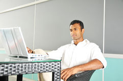 Indian Asian Man looking at his laptop outdoors Stock Image