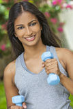Indian Asian Young Woman Girl Exercising With Weights. Beautiful Indian Asian young woman or girl running exercising with weights outside in summer sunshine with Stock Photo