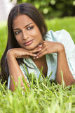 Indian Asian Young Woman Girl Resting on Hands Outside. Outdoor portrait of a beautiful Indian Asian young woman or girl outside in summer sunshine laying down Royalty Free Stock Image