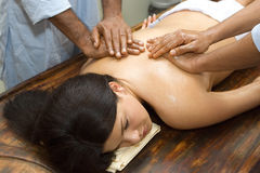 Indian ayurvedic oil body massage. Indian doctors make ayurvedic oil body massage royalty free stock photography