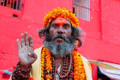 Indian Baba (Holy-man). An Indian Baba raises his hand whilst adorned in flowers and beads Stock Images