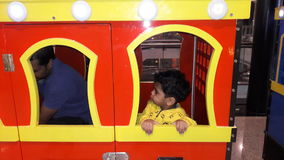 Indian baby boy playing in toy train stock images