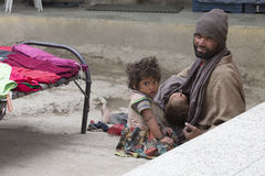 Indian beggar man with children on the street in Leh, Ladakh. India Stock Photography