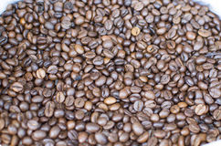 The Indian black coffee beans fried by a scattering on a market counter Royalty Free Stock Images