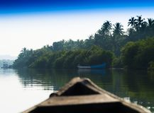 In Indian boat swimming down the jungle river background. Sailing goa green palm clear sky blue horizontal vivid vibrant bright color rich composition design stock photography