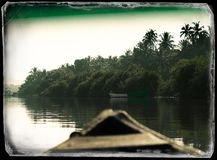 In Indian boat swimming down the jungle river vintage postcard b. Ackground sailing goa green palm clear sky blue horizontal vivid vibrant bright color rich royalty free stock images