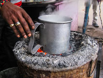 Indian boil in mug drink outside on stove. India. The man on street oven boils drink in an aluminum mug. Traditional Indian outdoor oven royalty free stock images
