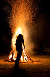 Indian and Bonfire. An Indian silhouetted in front of a large bonfire preparing for ritual dances to the Mountain Spirit Gods Stock Photos