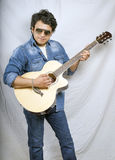 Indian boy in blue jeans and playing guitar Royalty Free Stock Images