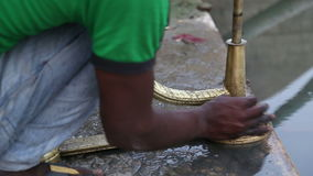 Indian boy cleaning decorative dishes at shore of Ganges in Varanasi. stock footage