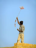 Indian boy flying kite from the roof of traditional house in Tha Royalty Free Stock Photos