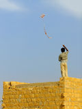 Indian boy flying kite from the roof of traditional house in Tha Royalty Free Stock Images