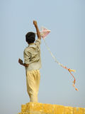 Indian boy flying kite from the roof of traditional house in Tha Royalty Free Stock Photo