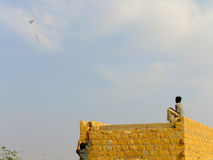 Indian boy flying kite from the roof of traditional house Stock Images