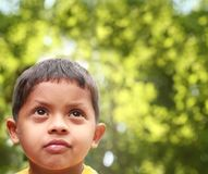 Indian boy of kinder-garten school age thinking Stock Image