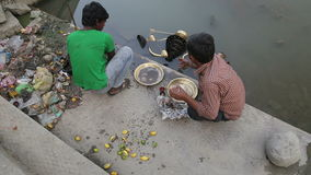 Indian boy and man cleaning decorative dishes at shore of Ganges in Varanasi. stock footage