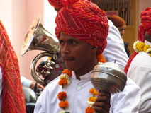 An Indian boy playing music in traditional dress and hat Royalty Free Stock Image